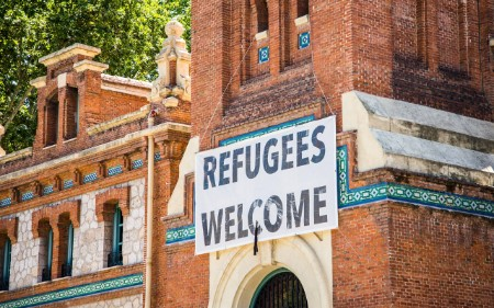 A building with a sign that reads refugees welcome