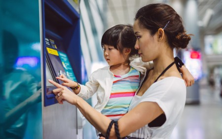 Mother and daughter using digital ticket machine