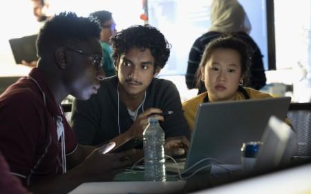 Diverse team working together around a laptop