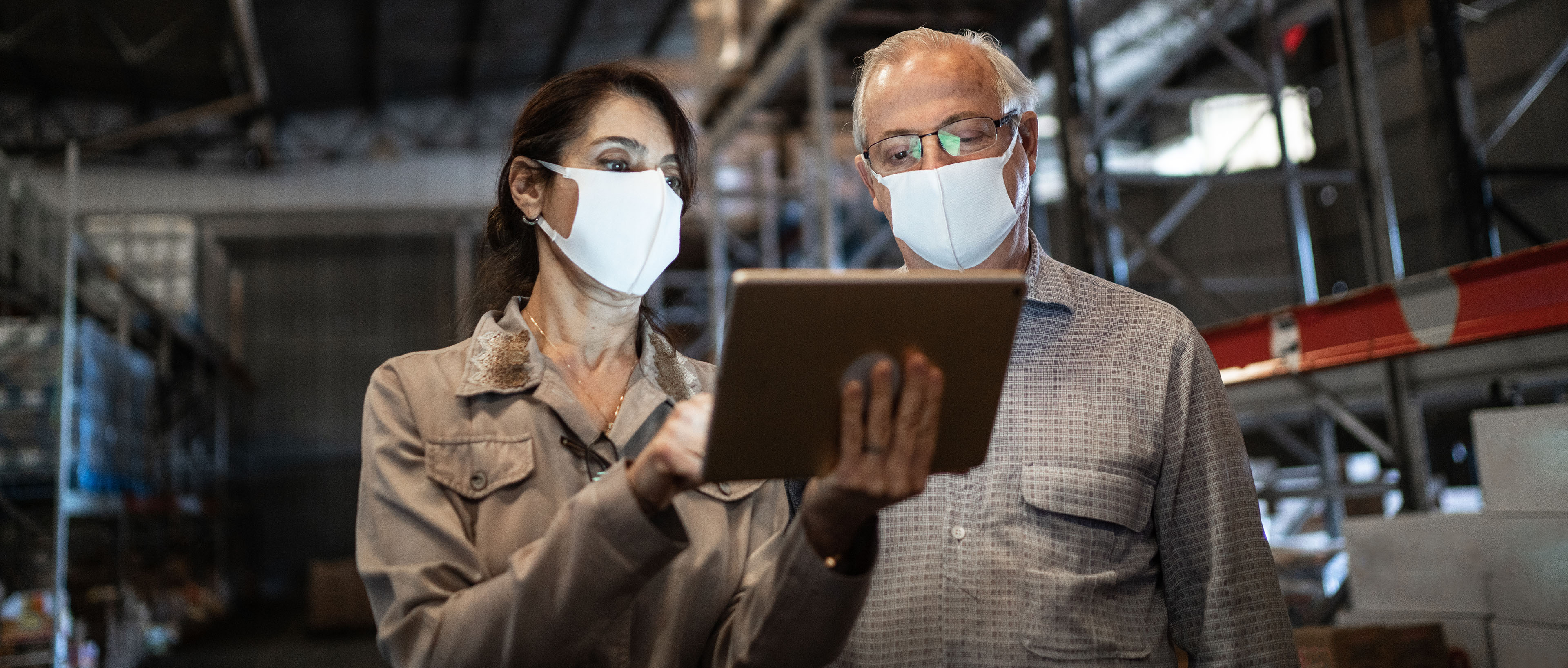 Man and woman using digital tablet in warehouse wearing masks