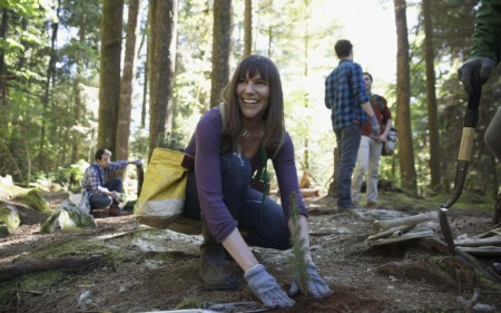 Smiling volunteer planting a tree