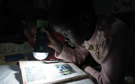 By torchlight, an adult helps a child with homework