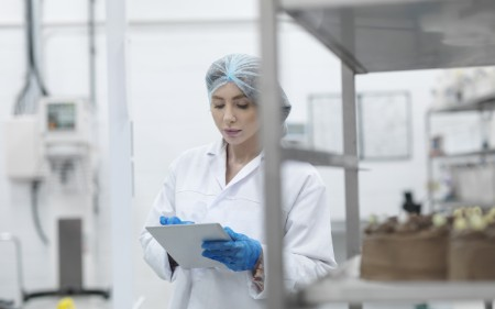 Woman in a food factory uses tablet