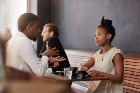 FNH6T6 African woman having meeting with a man in busy cafe