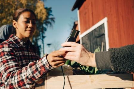 woman paying farmer credit card