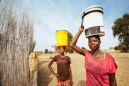 women carrying buckets water heads