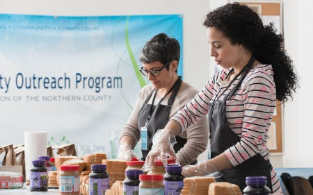 Two women volunteer at a food bank