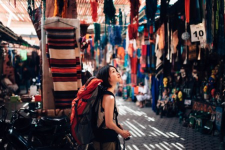 Female backpacker in market