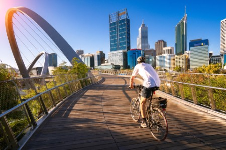 A man cycling on an Elizabeth bridge in Perth city