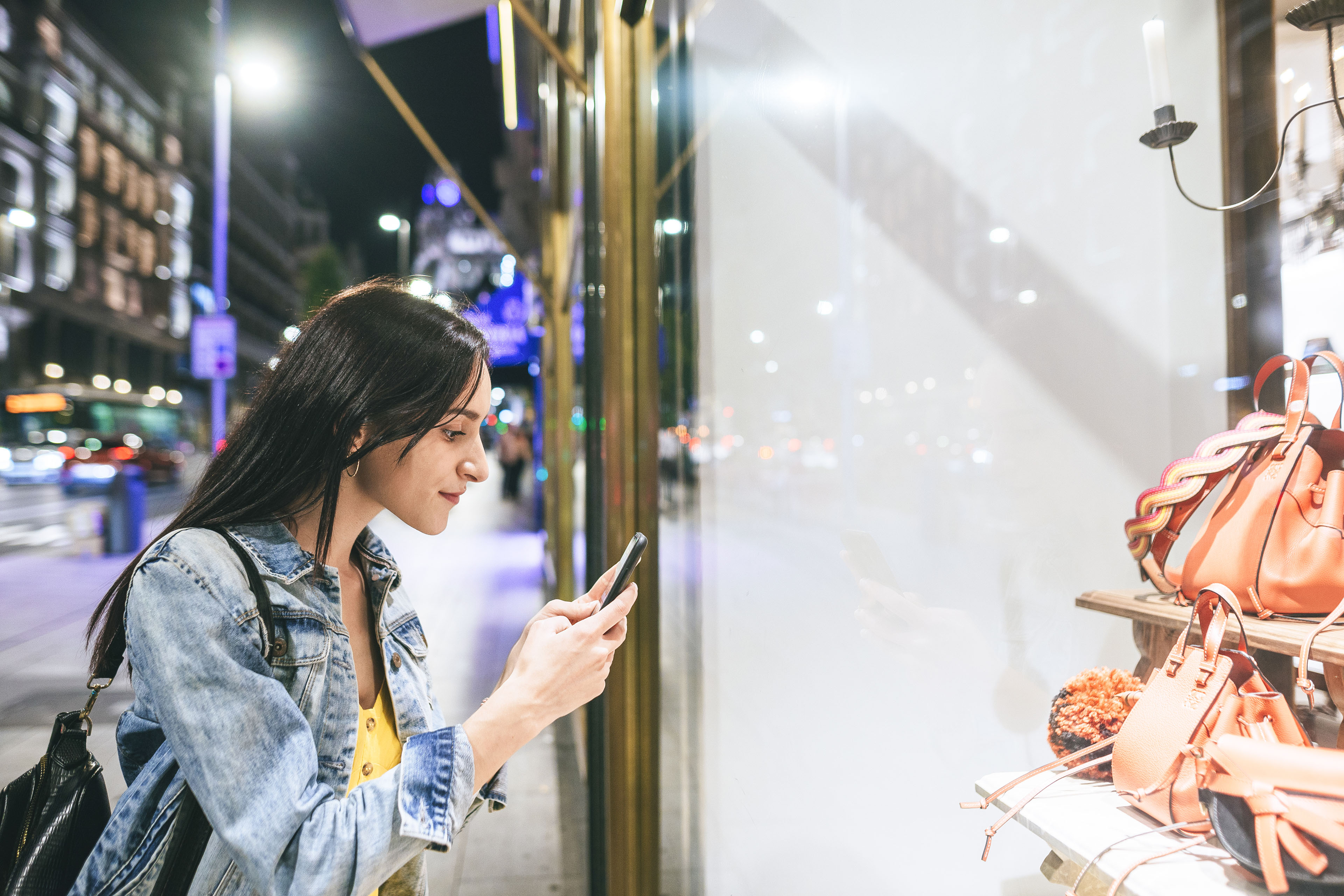 Woman taking a picture to shop window at night