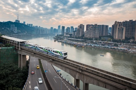 A commuter train streaks alongside a river and a city in China.