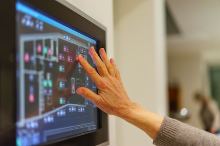A hand reaching out to a touchscreen.