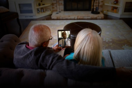 Mature couple video chatting to doctor on digital tablet