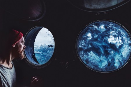 man looking out porthole