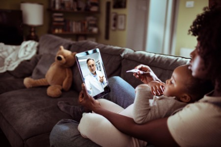 mother and daughter consulting with doctor on video call