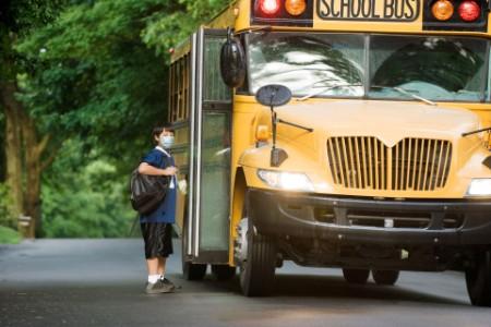 Un estudiante con una mascarilla quirúrgica en la parada de autobús