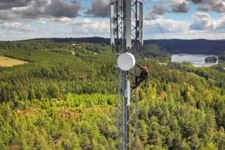 Telecommunications engineer on communication tower in the middle of forest