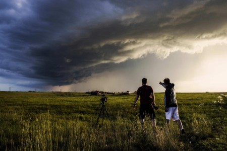 Two men enjoy a storm in the prairies at sunset