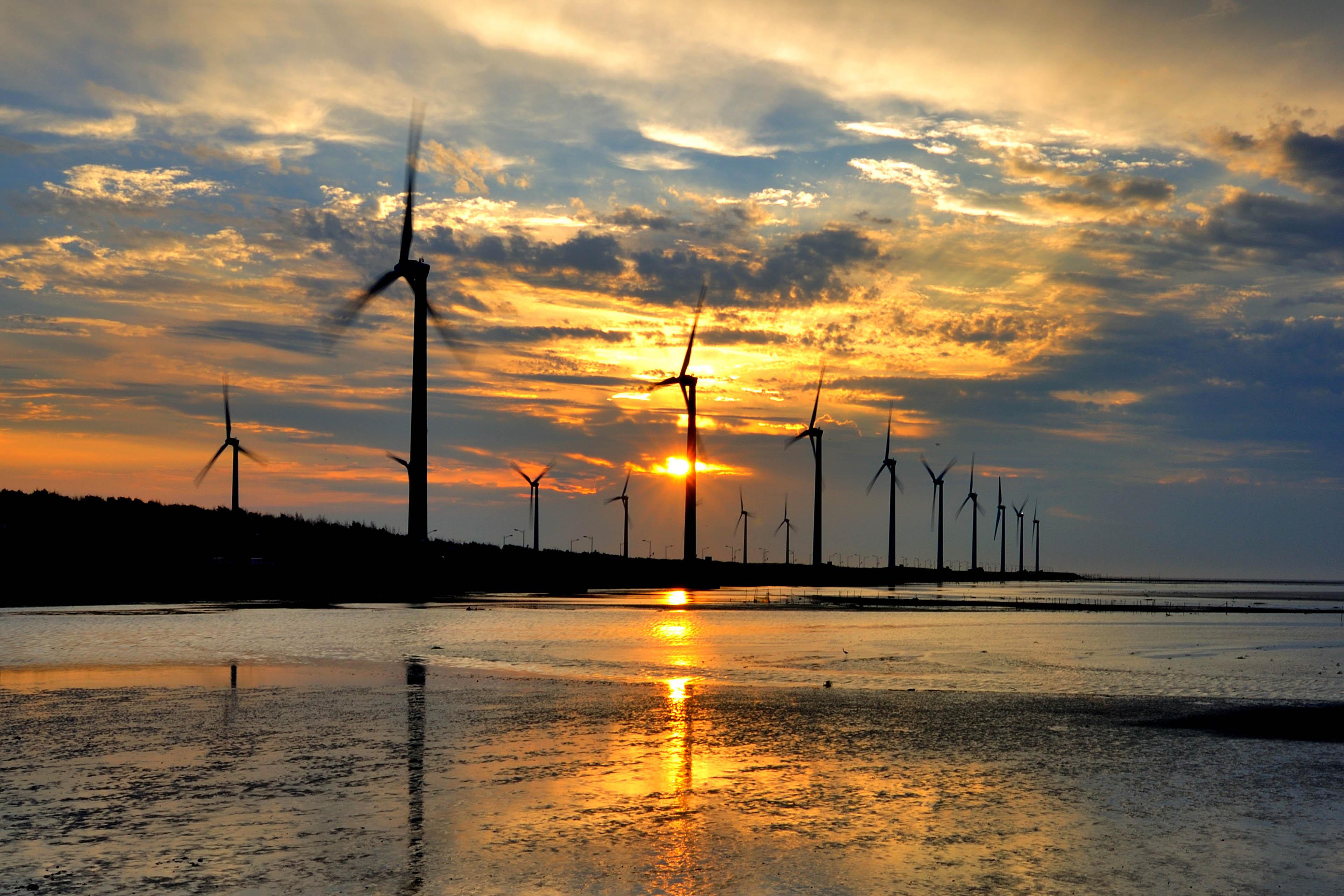 Wind turbines against sunset