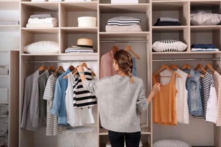 Mujer eligiendo ropa de un gran armario