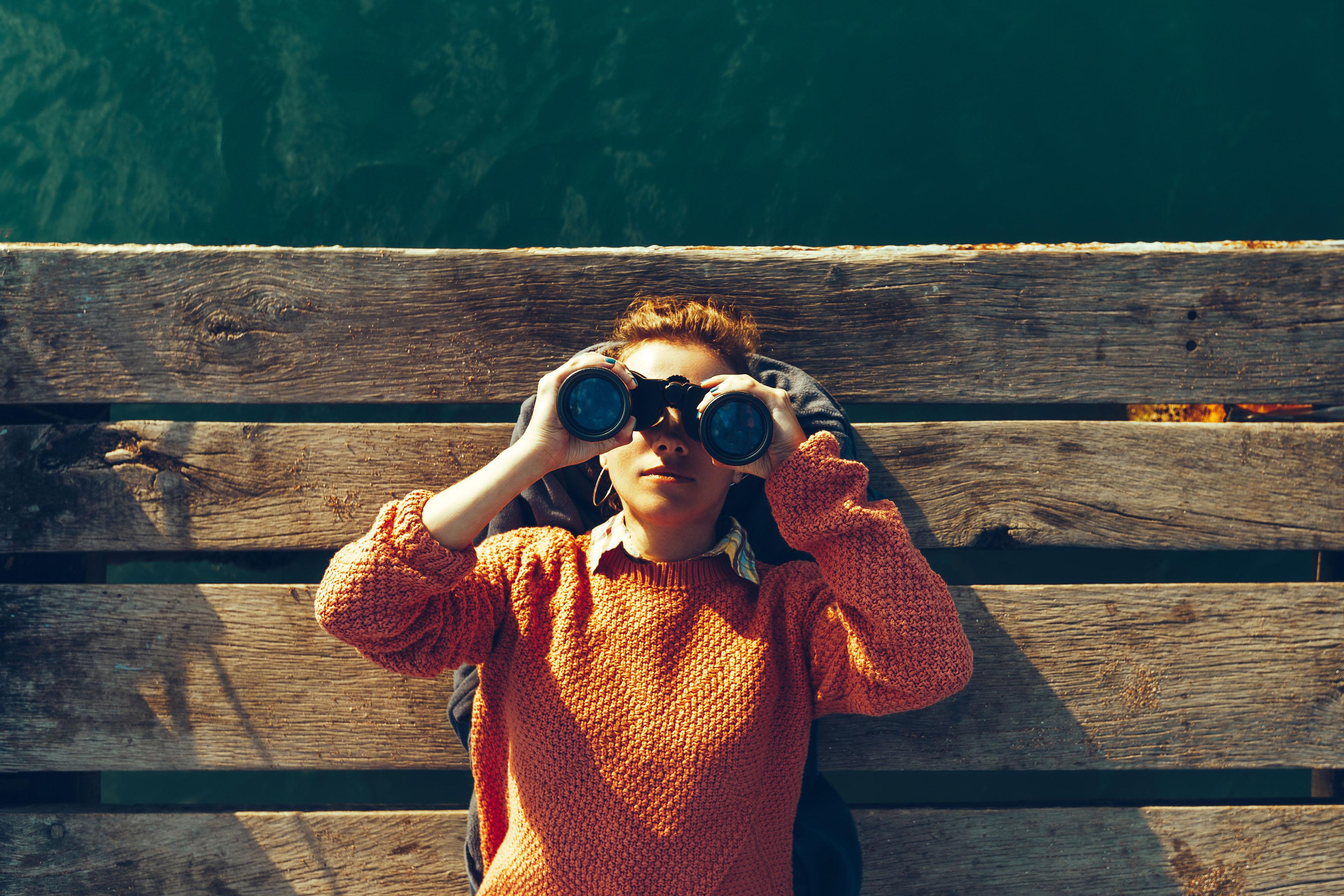 Young girl on pier looking through binoculars
