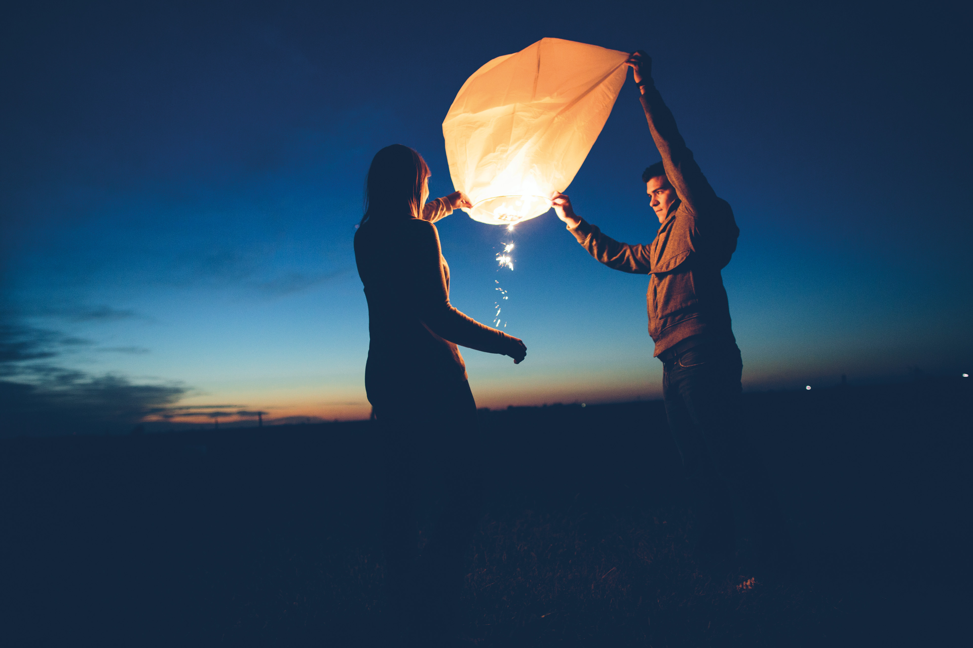 Young couple lighting Chinese lanterns at twilight