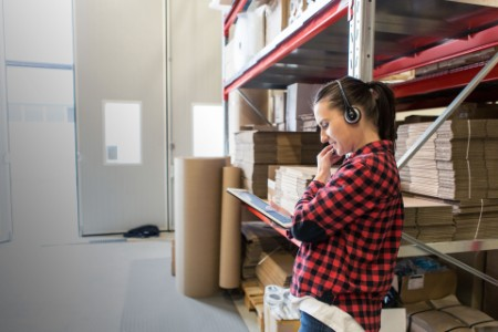 woman with headset and tablet in warehouse