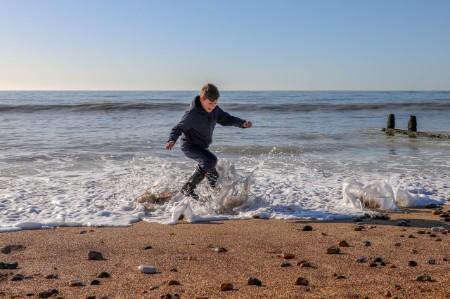 Boy playing waters edge