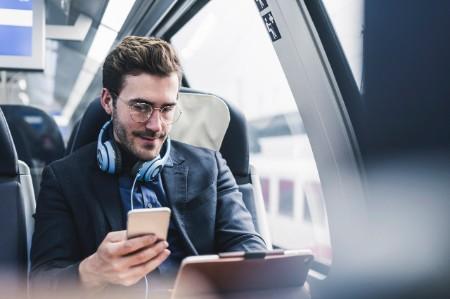 Businessman train phone headphones tablet