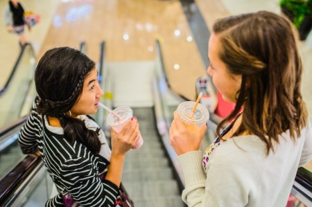 girls drinking smoothies escalator mall