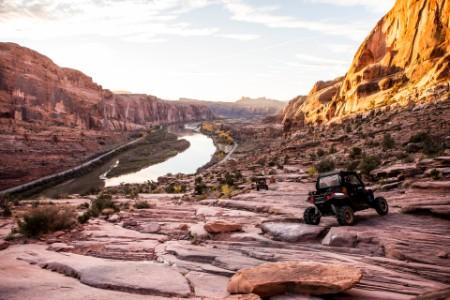 Een ATV rijdt over een rotsachtig pad met uitzicht op de Colorado rivier