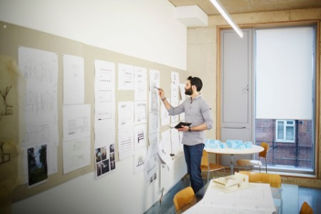 Architect reviews plans on a pinboard in an office