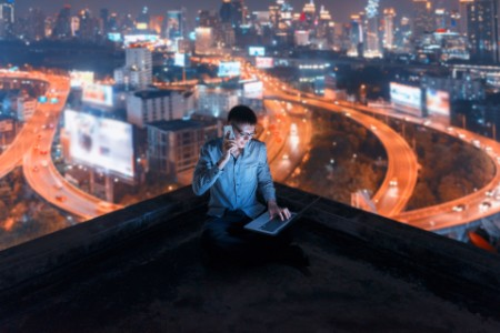 Asian man using phone and laptop with city background