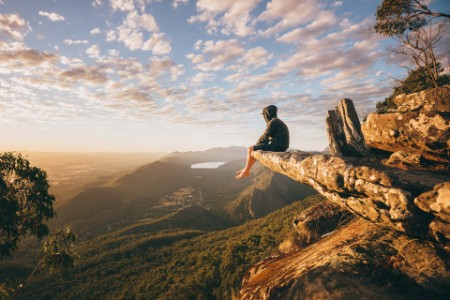 Backpacker boy sitting on a cliff
