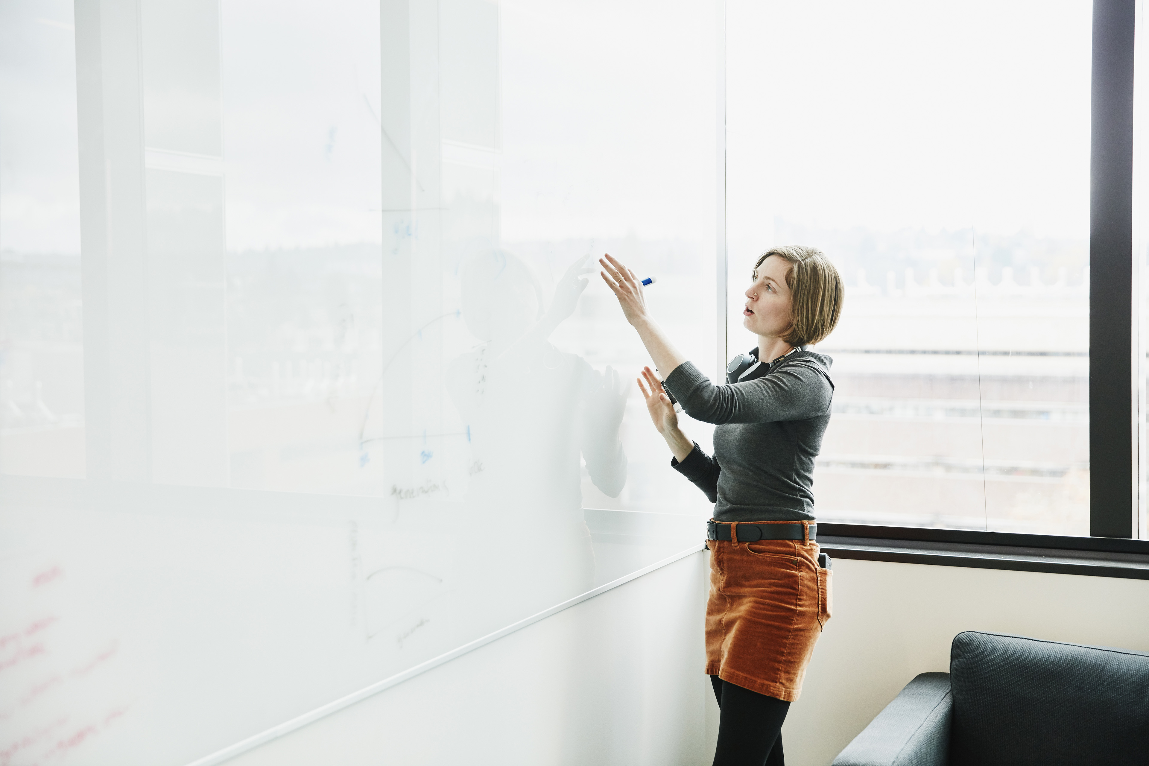 businesswoman leading project discussion at whiteboard in room