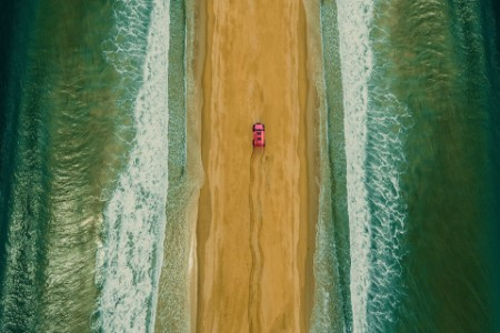 drone image of car driving down spot of land between sea
