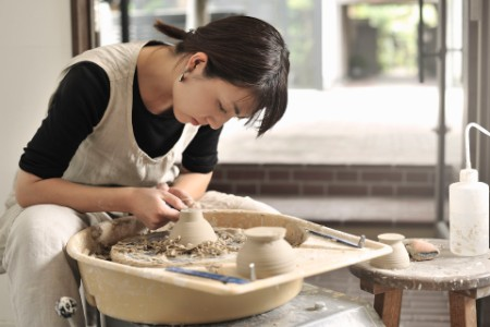 Female Potter working in studio with pottery wheel