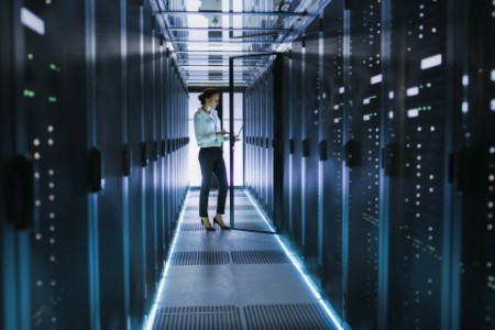 Female Server Technician Stands next to Cabinet in Data Center