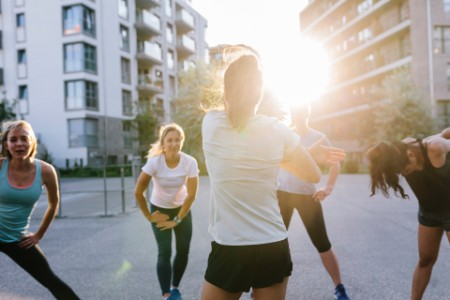 Photographic portrait of fitness instructor warming up class outdoors