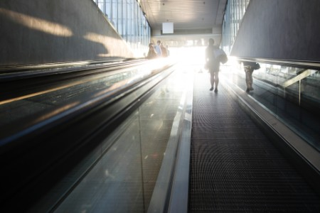 Photographic portrait of man or worker climbing escalator abroad