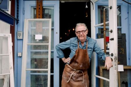 Mature craftsman stands in workshop doorway