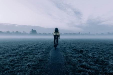 Vista trasera de un hombre en bicicleta por los campos