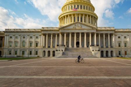 Una persona en bicicleta por la parte de atrás del edificio del capitolio de EE.UU.