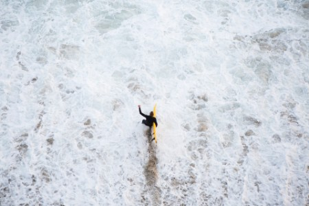 surfer in black wet suit walking into turbulent waters