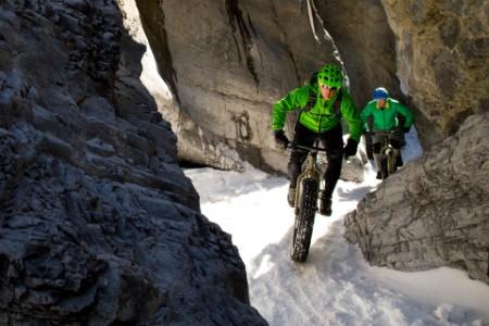 Mannen rijden fiets op de sneeuw