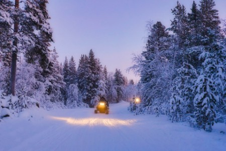 Two people riding snowmobiles through a snowy landscape