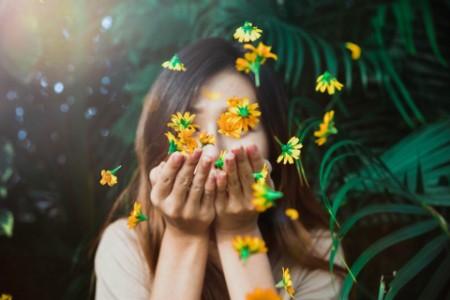 Women blowing beautiful yellow flowers