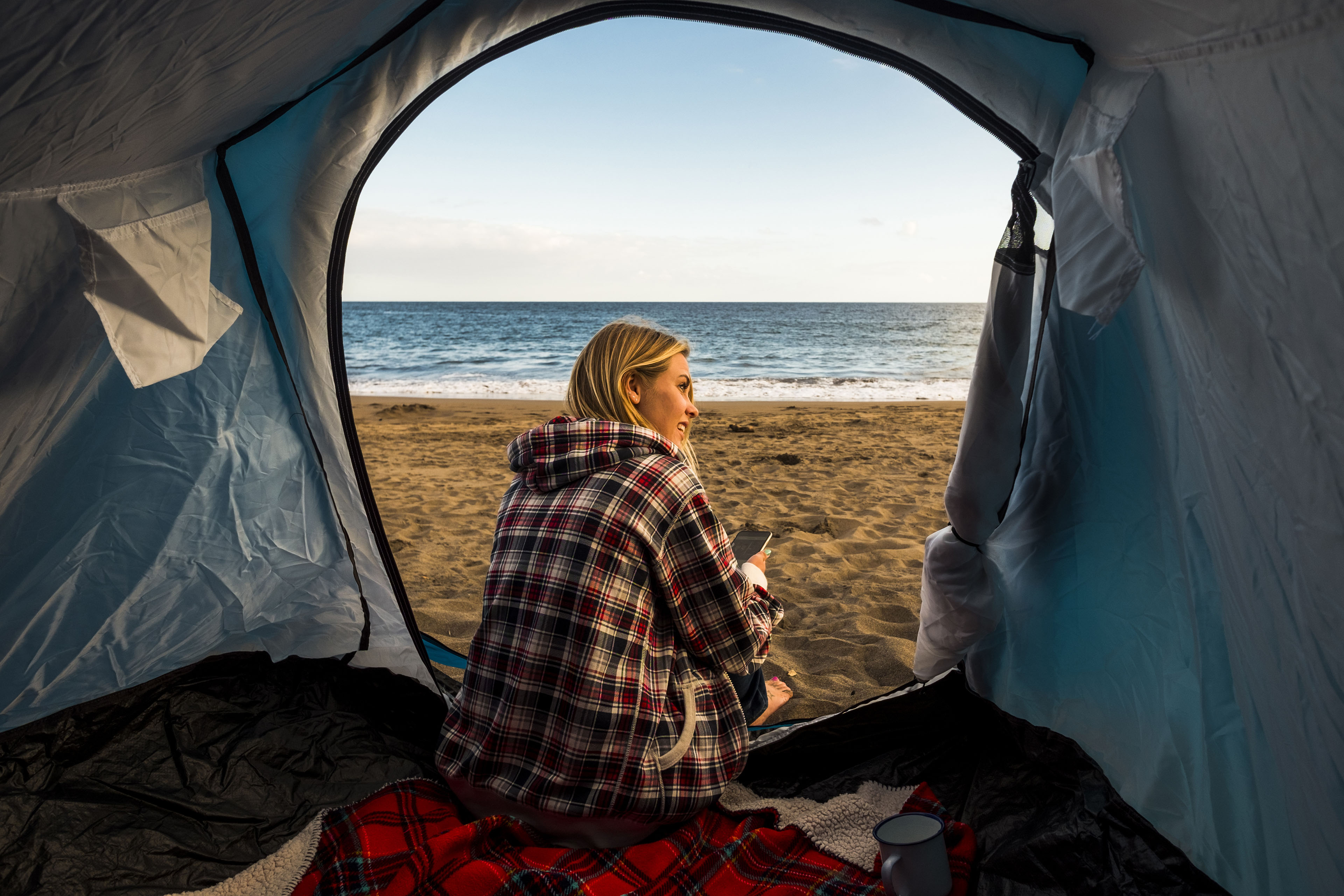 Woman sitting in her tent on the beach