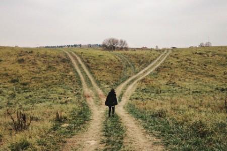 woman standing crossroads field