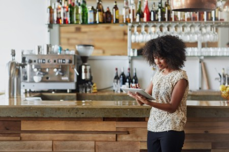 Woman standing in a bistro using a digital table